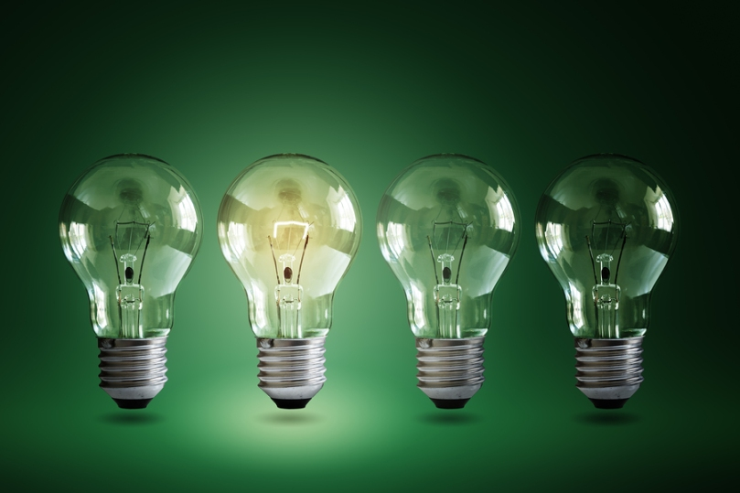Illuminated light bulb in a row of dim bulbs on a green background