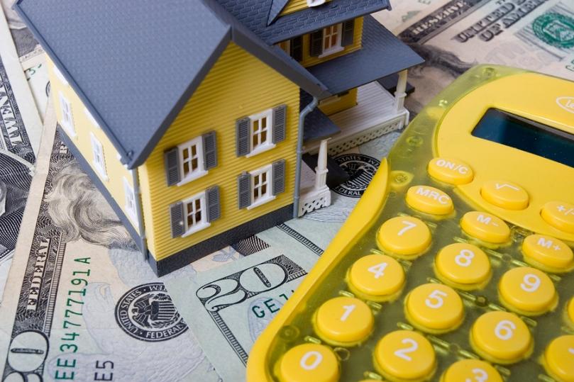 House with twenty dollar bills background and calculator