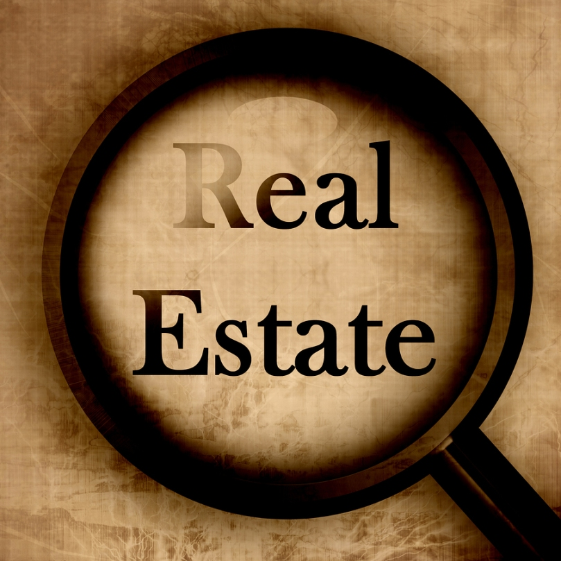 The words Real Estate highlighted under a large magnifying glass