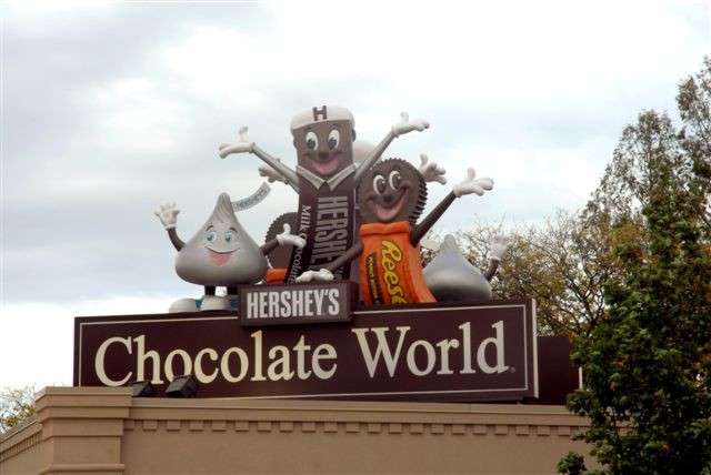 Chocolate World characters of Hershey Chocolate Bar, Hershey Kiss and Reese's Peanut Butter Cup atop Hershey's Chocolate World
