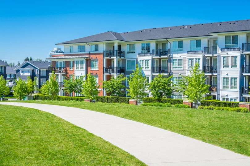 Residential apartment building on sunny day with blue sky, concrete walkway and lawn in front