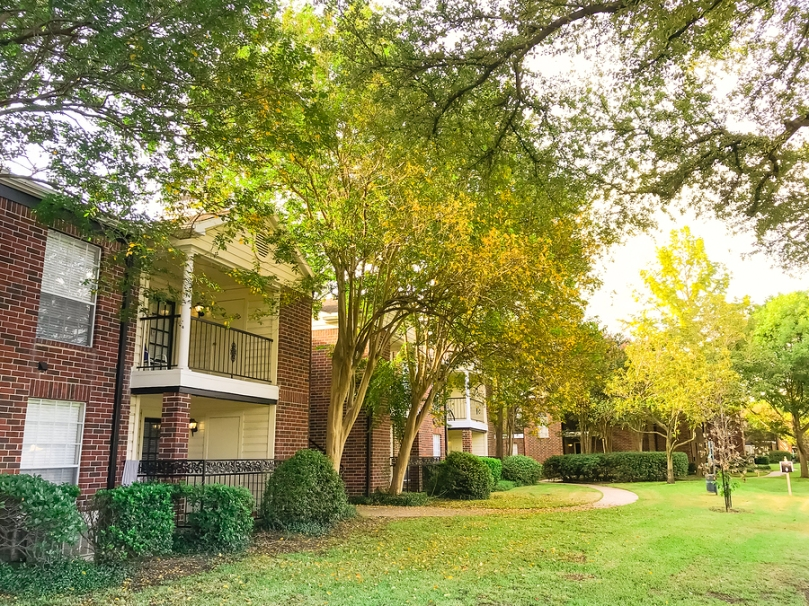 Typical 2-story apartment complex building in fall season. Grassy lawn patio yard and autumn yellow dry leaves falling on the pathway at sunset