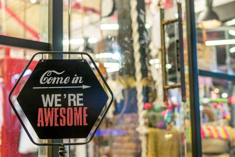 open sign in doorway of store